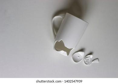 Broken White Cup with Few Little Pieces. Concept Disintegration. Broken Ceramic Mug
