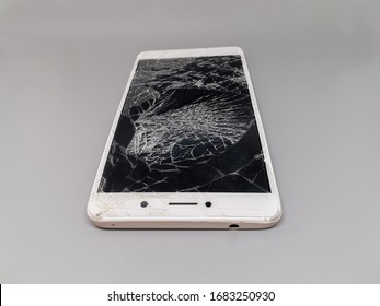 broken white mobile phone, screen crack on grey background
