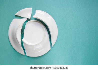 broken white plate on green background, copy space, top view