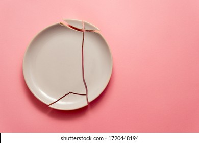 broken white plate on pink background, concept visual