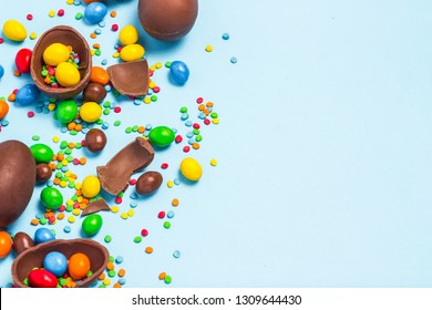 Broken and whole chocolate Easter eggs, multicolored sweets on blue background. Concept of celebrating Easter, Easter decorations, search for sweets for Easter Bunny. Flat lay, top view. Copy Space.