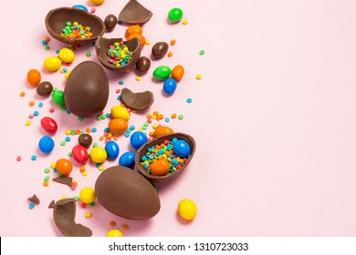 Broken and whole chocolate Easter eggs, multicolored sweets ,pink background. Shrub. Concept of celebrating Easter, Easter decorations. Flat lay, top view. Copy Space. Happy Easter.