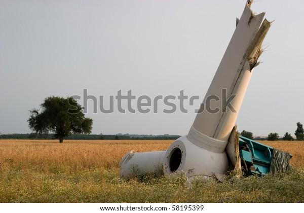 broken wind turbines on green field. Alternative source of energy
