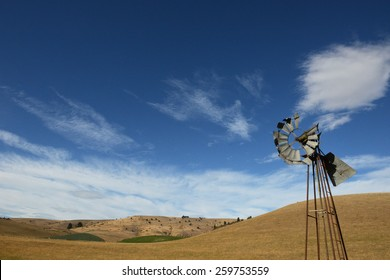A broken windmill in an arid, dry, pasture in New Zealand