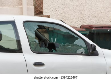 Broken window of a car parked in a street
