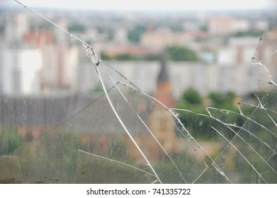 Broken window glass with city landscape behind it