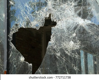 Broken window glass wall with heartshaped hole in it. War shooting concequences. Shaterred glass reflecting the sky. Heartache, suffering, depression concept.