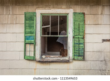 Broken window with green shutters on old rustic abandoned barn