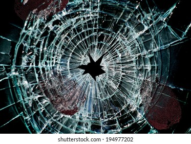 Broken window with a hole in the middle and finger prints