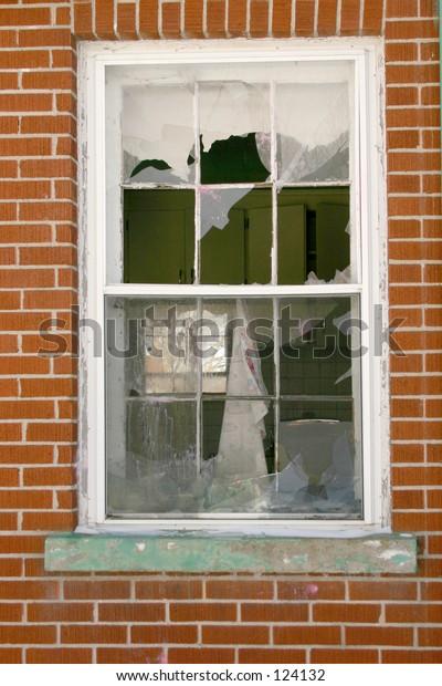 A broken window on a brick wall