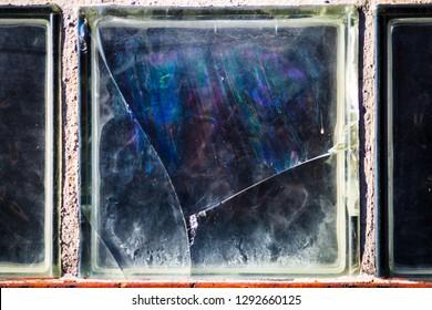 Broken window pane with distorted rainbows in glass