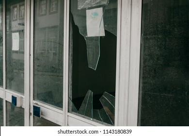 A broken window in a residential building or store as a result of an earthquake or vandalism or other negative event. Abandoned building.
