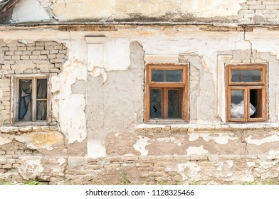 Broken windows of old abandoned house with damaged plaster and bad foundation