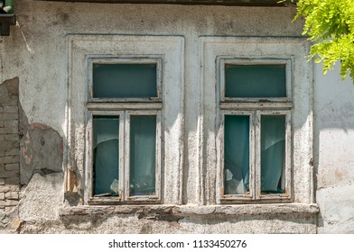 Broken windows of old abandoned house with damaged and peeling plaster