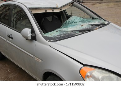 Broken windshield. A broken silver car after an accident on the road. Transport security concept.