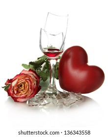Broken wineglass with dry rose and decorative heart isolated on white