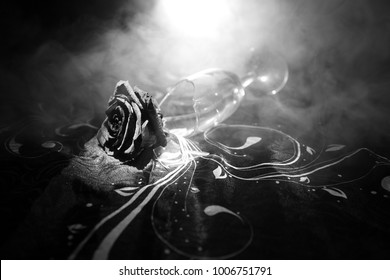 Broken wineglass and wilted rose on dark background. A wilting rose signifies lost love, divorce, or a bad relationship, dead rose on dark background with smoke. Selective focus