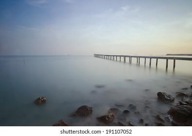 Broken wood bridge and waves crashing on sea at during sunset