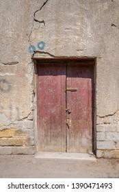 Broken wooden door on grunge stone bricks wall in abandoned Darb El Labana district, Cairo, Egypt