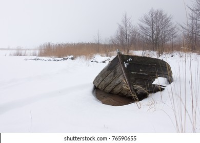 Broken wooden-boat at the beach.  (in the winter)