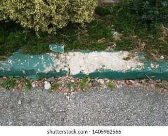 broken or worn green cement curb with asphalt
