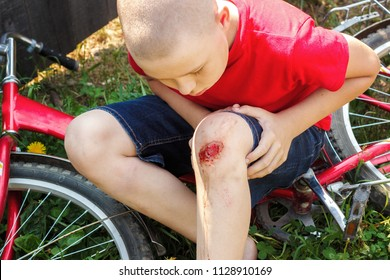 Broken wounded knee child. European boy in red T-shirt and denim shorts fell off bike and looks at wound abrasion. Concept children's summer holidays, childhood