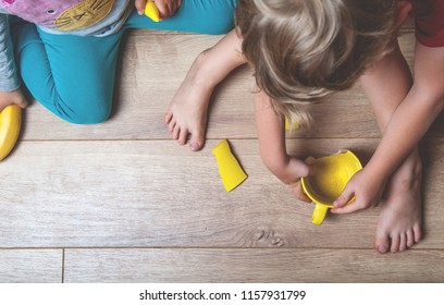 Broken yellow cup on the floor. Children are sitting on floor - fault of the kids. Little boy and girl trying to mend a dish. Kid's fear of punishment.
