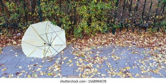 A broken yellow umbrella is by the side of the road.