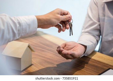 Broker agent's hand holding House key in insurance, giving to buyer customer, real estate agent.