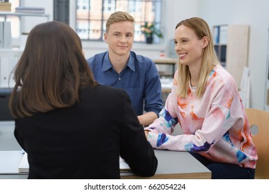 Broker giving a presentation to a young couple as they meet with her in an office in an over the shoulder view as they listen attentively to her