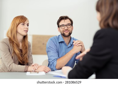 Broker having a discussion with a young couple who are sitting listening to her with serious attentive expressions
