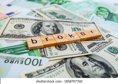 broker inscription on wooden cubes on the texture of us dollars and euro banknotes