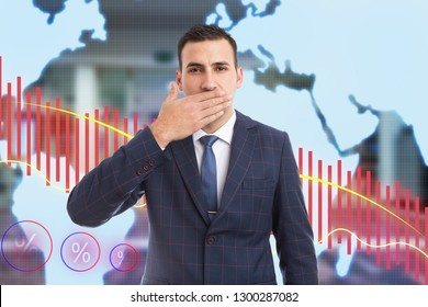 Broker man at business stock market covering mouth with palm as not-telling secret gesture in financial crisis concept on red decreasing graph background