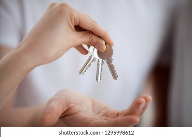 Broker realtor hand holding keys giving to new home buyer owner buying new house concept, customer renter making real estate deal, property ownership, mortgage loan investment contract, close up view
