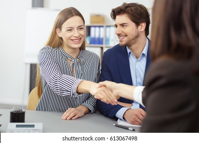 Broker shaking hands with a young couple in a meeting as the young wife stretches across the desk with a smile