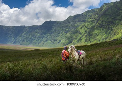 BROMO, INDONESIA - 16th APRIL 2018; Silhouette of unidentified local people or Bromo Horseman pose for camera at the mountainside of Mount Bromo, Semeru, Tengger National Park, Indonesia