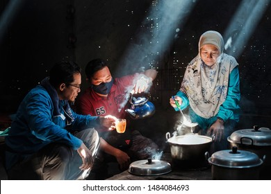 BROMO, INDONESIA - AUGUST 2nd, 2019: A female traveler prepares a lunch for the family with a traditional wood kitchen while her husband and children enjoy hot tea in the village of Cemoro Lawang.