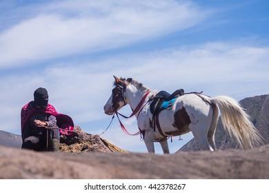 BROMO - JUNE 13, 2015: Horsemen having a cigarette brake at The Tengger Sand Sea, Bromo Indonesia