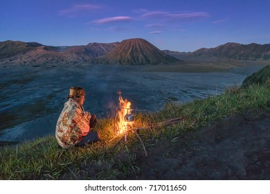 Bromo National Park, Probolinggo, East Java, Indonesia - July 14, 2017 : A farmer warming up at a campfire, at the top of the outer caldera of Mount Bromo (mount Bromo in the background)