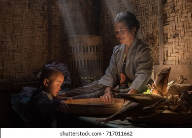 Bromo National Park, Probolinggo, East Java, Indonesia - July 14, 2017 : Grandma with her grandson in the simple kitchen or her small farmers house