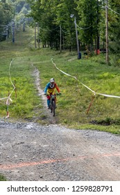 Bromont, Quebec - September 1, 2018 - Vertical of a colorful dirt bike racers competing on a ski hill mountain trail in Bromont