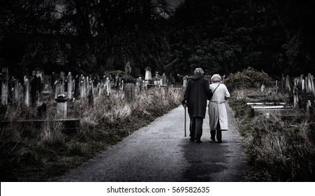 Brompton, London - Elderly couple walk away through old spooky graveyard arm-in-arm