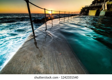 Bronte Pool, Sydney at sunrise with the orb of the sun just appearing over the horizon lighting up the rock pool as it juts out into the ocean with surf cascading over the wall