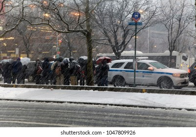 BRONX, NEW YORK - MARCH 7: A crowd of people wait for bus at Yankee Stadium in snow storm.  Taken March 7, 2018 in New York.