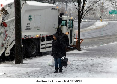 BRONX, NEW YORK - MARCH 7: Woman passess snow removal truck during winter storm.  Taken March 7, 2018 in New York.