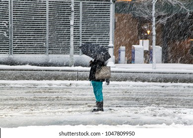 BRONX, NEW YORK - MARCH 7: Woman waits for taxi near Yankee Stadium subway station during snow storm.  Taken March 7, 2018 in New York.