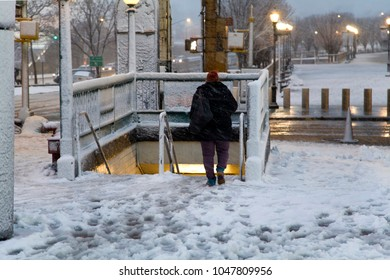 BRONX, NEW YORK - MARCH 7: Woman decends to underground subway station at Yankee Stadium during snow storm.  Taken March 7, 2018 in New York.