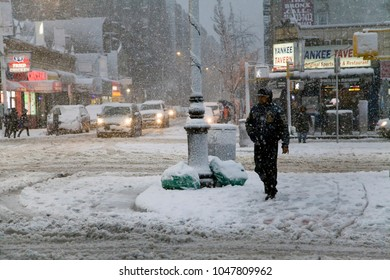 BRONX, NEW YORK - MARCH 7: Minority man crosses street during snow storm.  Taken March 7, 2018 in New York.