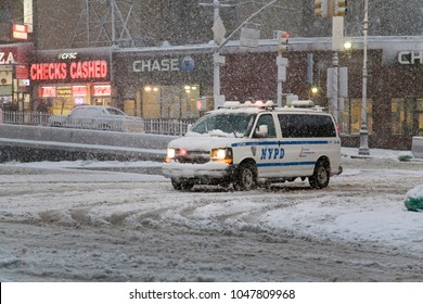 BRONX, NEW YORK - MARCH 7: Police vehicle crosses intersection of road during snow storm.  Taken March 7, 2018 in New York.