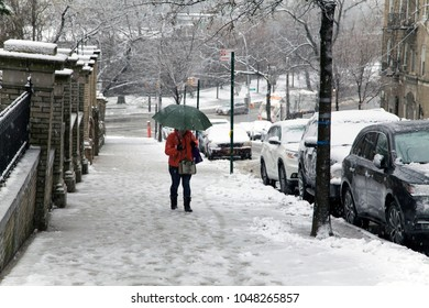 BRONX, NEW YORK - MARCH 7: Woman walks up pathway with umbrella during snow fall.  Taken March 7, 2018 in New York.
